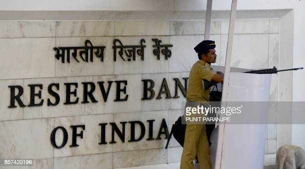 An Indian policeman stands guard at the entrance of the Reserve Bank of India head office in Mumbai on October 4 2017 India's central bank held...