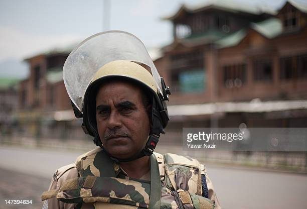 An Indian policeman stands guard during an undeclared curfew on June 29 2012 in Srinagar the summer capital of Indian administered Kashmir India Life...