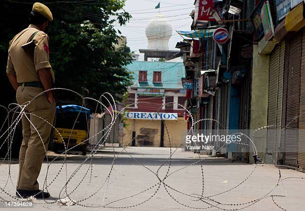 An Indian policeman stands guard next to razor wire during an undeclared curfew on June 29 2012 in Srinagar the summer capital of Indian administered...