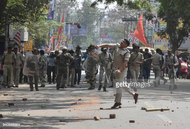An Indian policeman throws back a rock thrown by protesters during a protest as part of a countrywide strike against a Supreme Court order that...