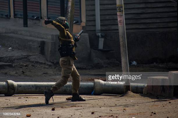 An Indian policeman throws stones at Kashmiri protesters during clashes between Indian government forces and Kashmiri Muslims near the site after a...