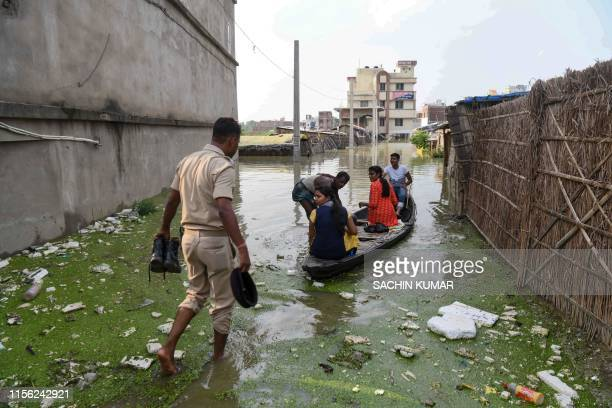 An Indian policeman travels with residents on a wooden boat to cross a flooded locality near the Ahiyapur police station at Muzaffarpur district in...