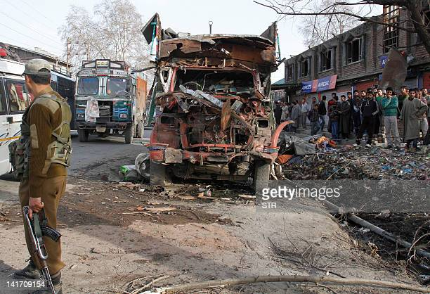 An Indian policeman walks near the wreckage of a truck after a carbomb explosion in Bijbehara 49km south of Srinagar the summer capital of Indian...
