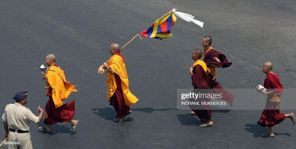 An Indian policeman watches Tibetan monk : News Photo