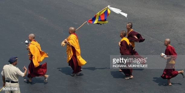 An Indian policeman watches Tibetan monks on a protest march in Mumbai on April 10 2008 Tibetans in exile under the banner of Tibetan Solidarity...