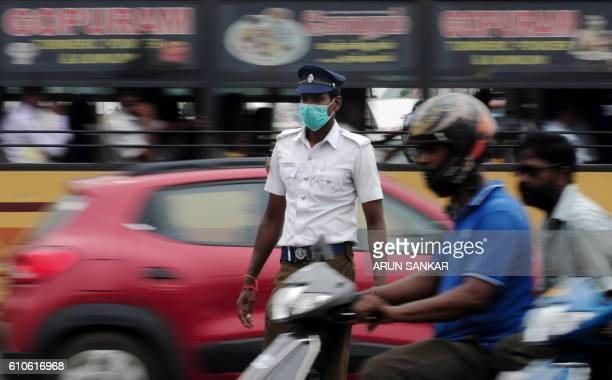 An Indian policeman wear a mask to protect himself against dust and pollution as he directs traffic in Chennai on September 27 2016 Nine out of 10...