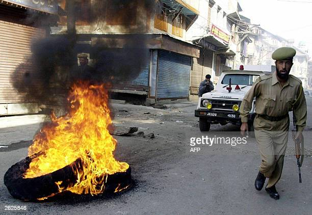 An Indian policemen runs by burning tyres 22 October 2003 during a protest against the arrest of influencial proindependence leader Yasin Malik in...