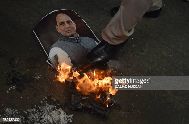 TOPSHOT An Indian policemen tries to extinguish a burning poster bearing the image of Indian Home Minister Rajnath Singh during a demonstration by...