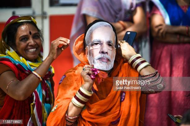 An Indian political supporter wears a mask of Indian Prime Minister Narendra Modi as she participates in Bharatiya Janata Party President Amit Shah's...
