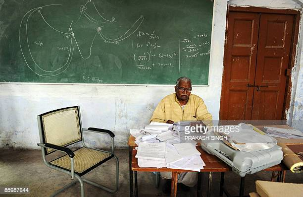 An Indian polling officer checks documents and the list of voters on the eve of polling in Varanasi on April 15 2009 India holds its 15th...