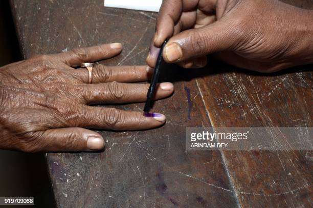 An Indian polling official marks indelible ink on a woman's finger after casting her vote at a polling station during Tripura legislative assembly...