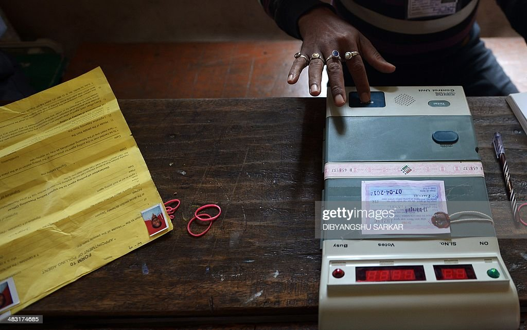 An Indian polling official tests an Electronic Voting Machine (EVM) in front of polling agents prior to the start of voting at a polling station in Dibrugarh on April 7, 2014, as they prepare for voters arrival during national elections. Indians have begun voting in the world's biggest election which is set to sweep the Hindu nationalist opposition to power at a time of low growth, anger about corruption and warnings about religious unrest. India's 814-million-strong electorate are forecast to inflict a heavy defeat on the ruling Congress party, in power for 10 years and led by India's famous Gandhi dynasty. AFP PHOTO/ Dibyangshu SARKAR