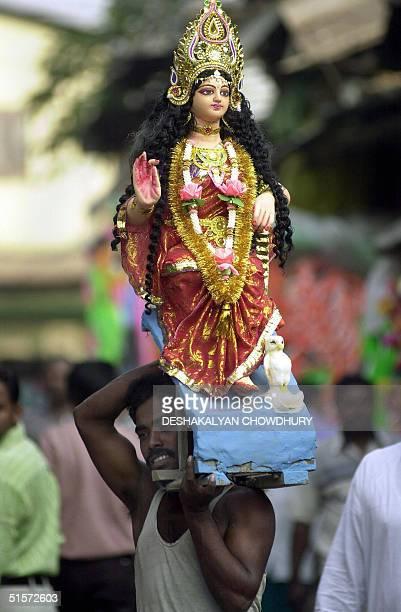 An Indian porter carries a clay idol of the Hindu goddess Lakshmi through a busy street of Calcutta 26 October 2004 Goddess Lakshmi the goddess of...
