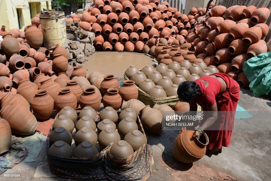 An Indian potter applies colour to traditional earthenware pots in Hyderabad on March 14, 2017. Earthenware pots, locally known as matkas, are used to store and cool drinking water when temperatures dramatically increase during summer. /