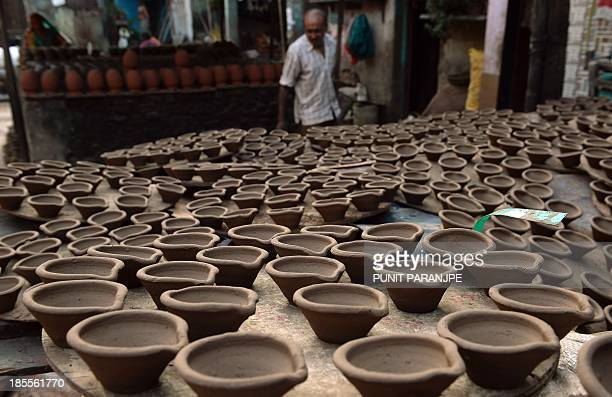 An Indian potter arranges earthen lamps used extensively during the Hindu festival of lights Diwali at a workshop in the Dharavi area in Mumbai on...