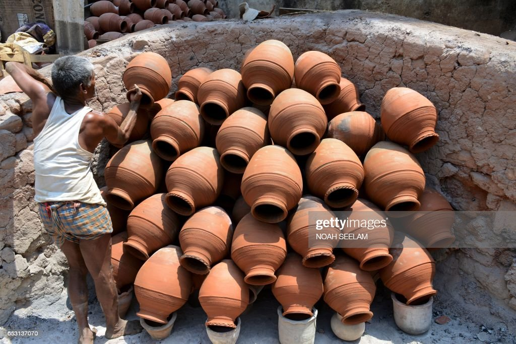 An Indian potter arranges traditional earthenware pots for firing in Hyderabad on March 14, 2017. Earthenware pots, locally known as matkas, are used to store and cool drinking water when temperatures dramatically increase during summer. /