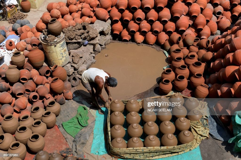 An Indian potter arranges traditional earthenware pots to dry in Hyderabad on March 14, 2017. Earthenware pots, locally known as matkas, are used to store and cool drinking water when temperatures dramatically increase during summer. /