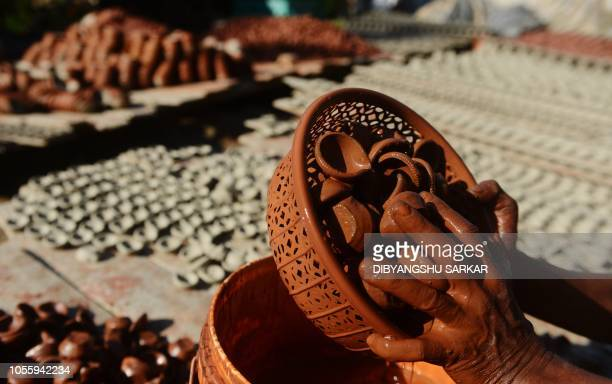 An Indian potter colours diyas ahead of the Hindu festival Diwali on the outskirts of Kolkata on November 1, 2018. - Hindus celebrate Diwali known as...