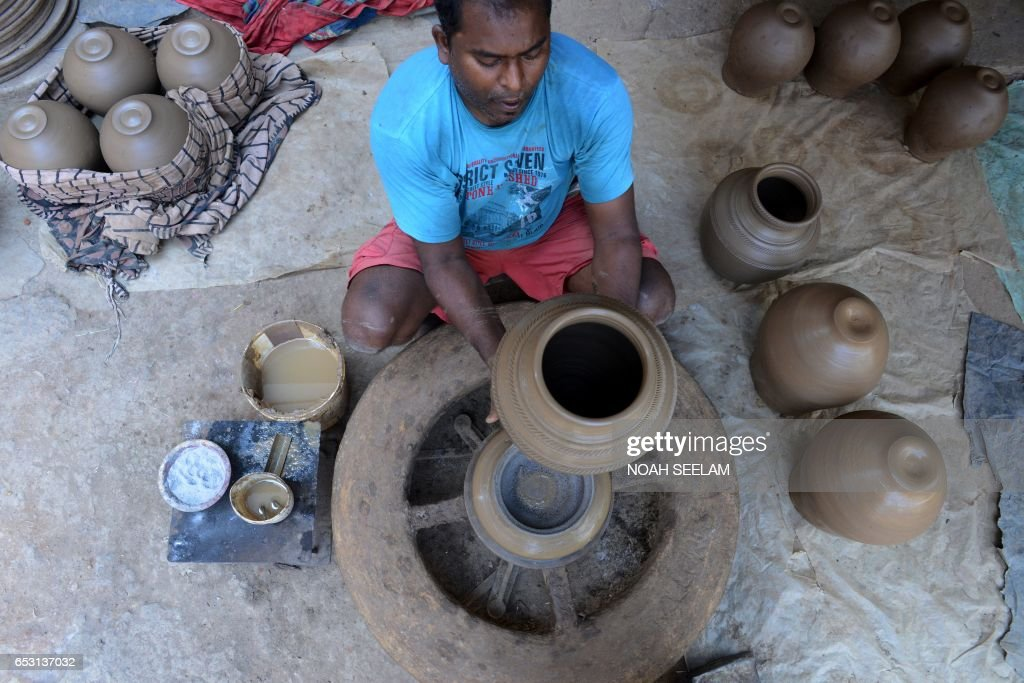 An Indian potter makes a traditional earthenware pot in Hyderabad on March 14, 2017