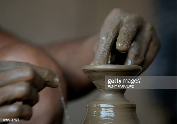 An Indian potter makes earthen lamps used extensively during the Hindu festival of lights Diwali at a workshop in the Dharavi area in Mumbai on...