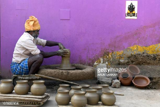 TOPSHOT An Indian potter makes earthen pots for sale ahead of the Hindu Pongal festival or Makar Sankranti in a village on the outskirts of Chennai...