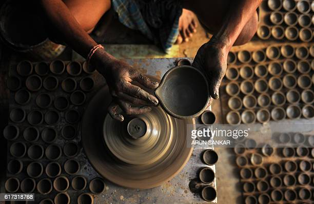 An Indian potter makes earthenware oil lamps or 'diyas' at a workshop ahead of the forthcoming Diwali festival in Chennai on October 23 2016 Diyas...