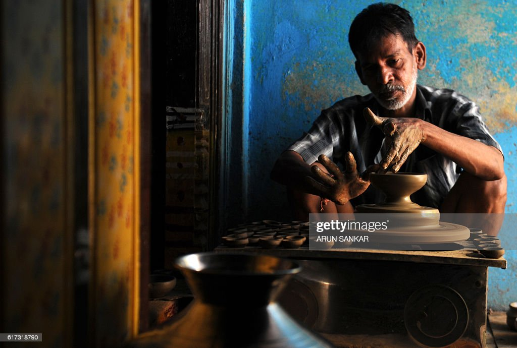 An Indian potter makes earthenware oil lamps or 'diyas' at a workshop, ahead of the forthcoming Diwali festival, in Chennai on October 23, 2016. Diyas, which are lit and placed around the home, are in heavy demand during the Diwali festival which marks the victory of good over evil. / AFP / ARUN