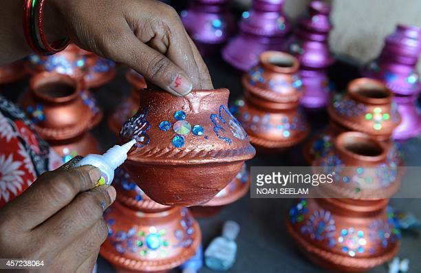 An Indian potter makes earthenware oil pots or 'diyas' ahead of the forthcoming Diwali festival on the outskirts of Hyderabad on October 15 2014...