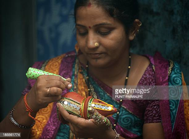 An Indian potter paints decorations on an earthen lamp used extensively during the Hindu festival of lights Diwali at a workshop in the Dharavi area...