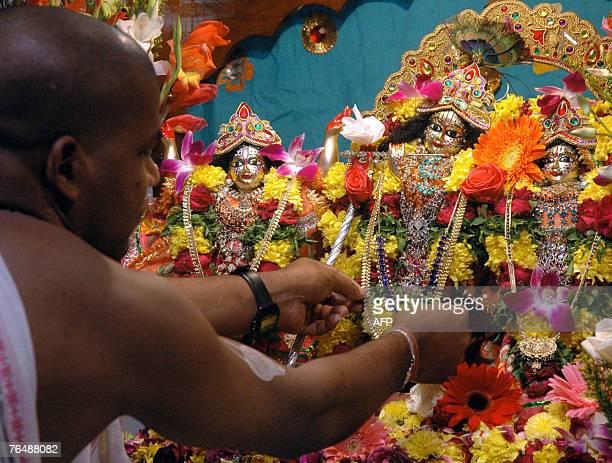 An Indian priest decorates the idols of Hindu God Lord Krishna , Radha and ChaitnayaPrabhu for the Janmashtami - the birthday of Lord krishna -...