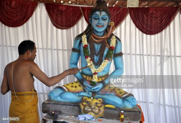 An Indian priest offers prayers to a statue of the Hindu god Lord Shiva to mark the Maha Shivaratri festival at the Shiva Mandir in Hyderabad on...