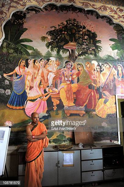An Indian priest sits below a mural depicting Hindu god Lord Krishna and Radha at the International Society for Krishna Consciousness on the occasion...