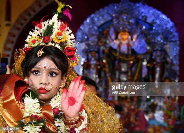 An Indian priest worships sixyearold Hindu girl Anushka Chetterjee dressed as the Hindu goddess Durga at a 'pandal' for the celebrations of the...