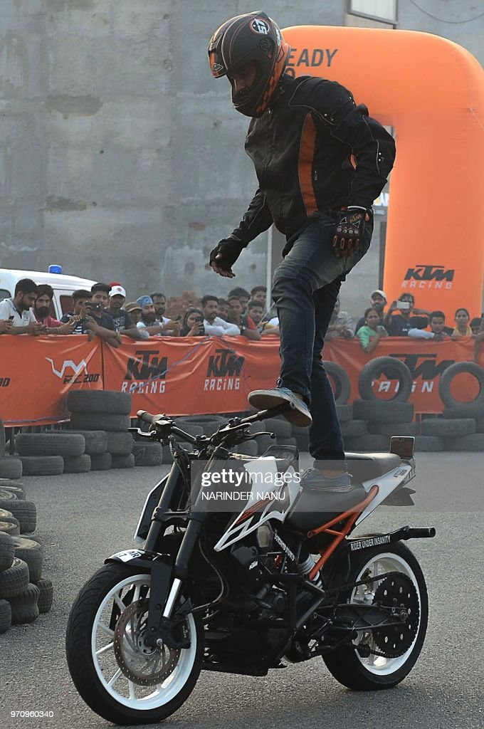 An Indian professional stuntmen performs on a motorbike during the KTM stunt show in Amritsar on June 10 2018