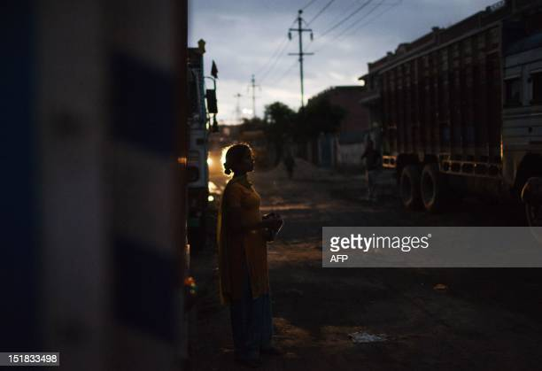 An Indian prostitute stands in the shadows near trucks as she waits for clients at the Sanjay Gandhi Transport Nagar a transport rest area in New...