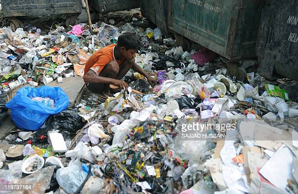 An Indian ragpicker searches for recyclable materials among rubbish in New Delhi on July 24 2011 Ragpickers with their daily collection of plastic...
