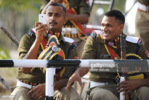 An Indian Railway Protection Force personnel uses a cell phone to take photographs of his colleagues during Republic Day celebrations in Secunderabad...