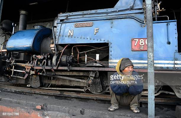 An Indian railway worker looks on as he sits alongside a steam engine of the Darjeeling Himalayan Railway train locally known as the 'toy train' in...