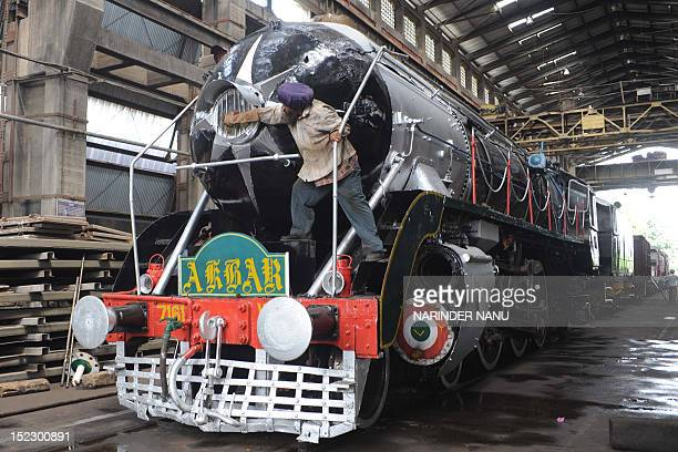 An Indian railway worker Sukhdev Singh cleans dust from the one of the most popular heritage steam rail engines called 'Akbar' after the great Mughal...