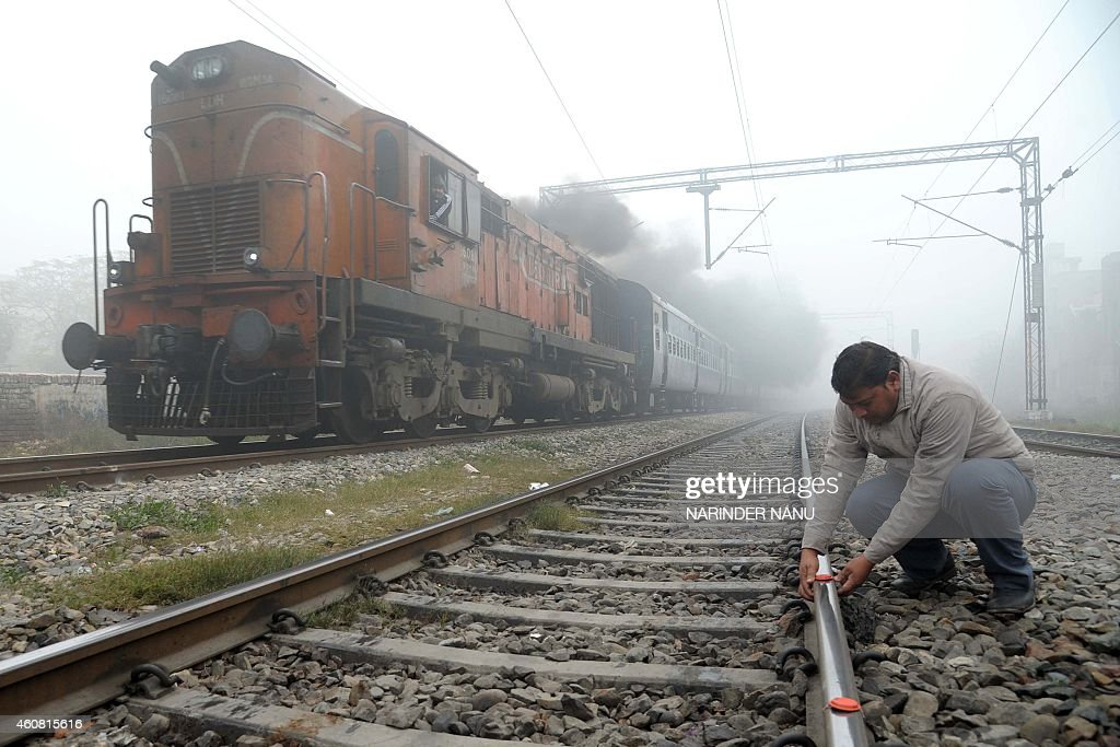 An Indian Railways employee places `fog signals` on a railway track as a train passes in dense fog at a railway station in Amritsar on December 24...