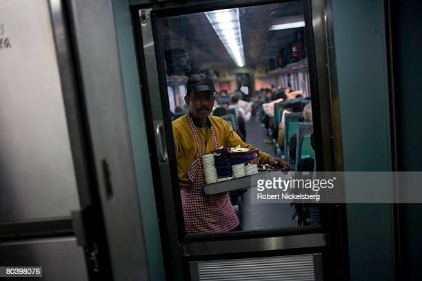 An Indian Railways waiter clears breakfast dishes onboard the early morning Shatabdi Express train from New Delhi to Agra February 16 2008 near Agra...