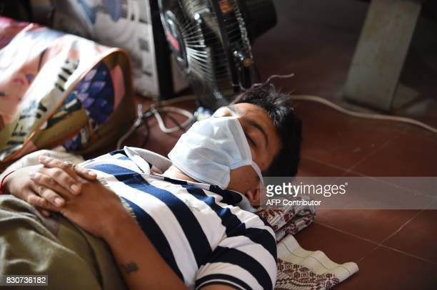 An Indian relative of a Swine flu patient under treatment takes a nap outside the isolation ward of the Ahmedabad Civil Hospital in Ahmedabad on...