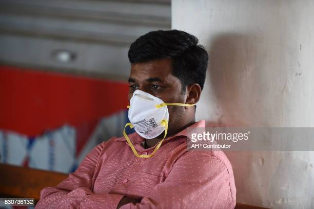 An Indian relative of the swine flu patient under treatment sits outside the isolation ward of the Ahmedabad Civil Hospital in Ahmedabad on August 12...