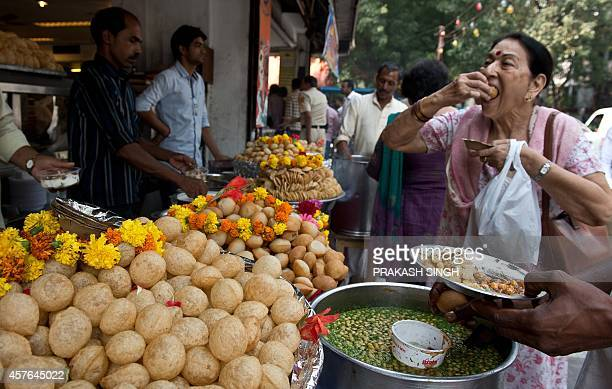 An Indian resident eats golgappas at a roadside snack shop in New Delhi on October 22 2014 AFP PHOTO / PRAKASH SINGH