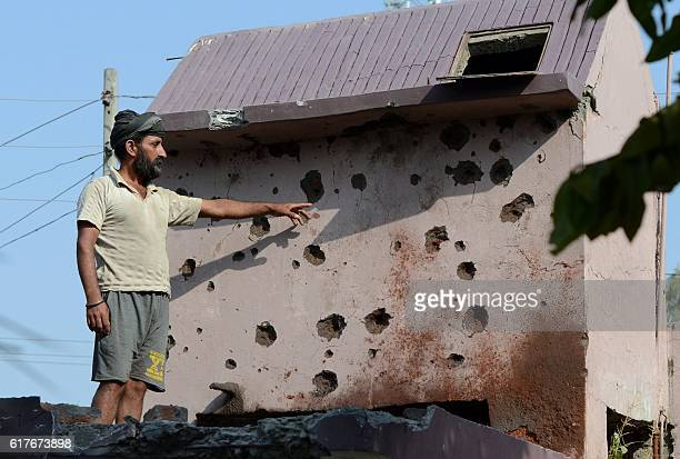 An Indian resident of Gajansoo border village points out damage to property from cross border firing in Kanachak sector about 25km from Jammu on...