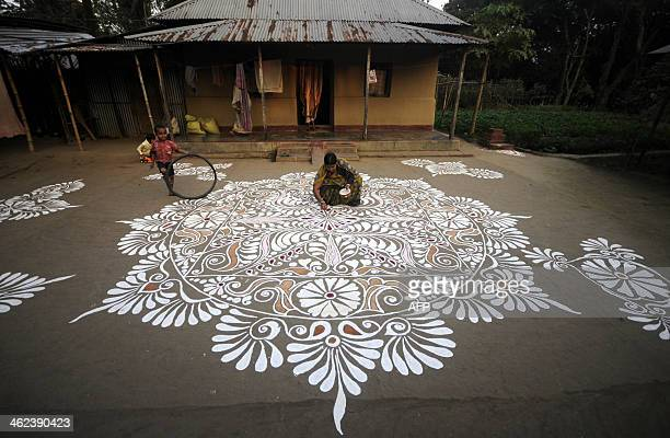 An Indian resident paints a 'Rangoli' design in front of her house on the eve of the Hindu festival Makar Sankaranti in Lankamura village on the...