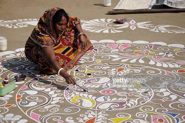 An Indian resident paints a 'Rangoli' design in front of her house on the eve of the Hindu festival of Makar Sankaranti in Lankamura village on the...