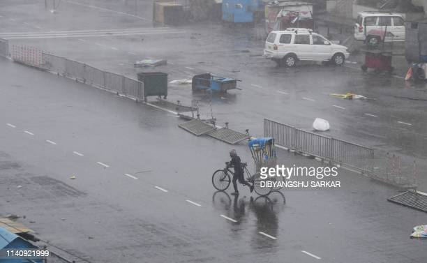 An Indian resident pulls his cycle rickshaw across a street after Cyclone Fani landfall in Puri in the eastern Indian state of Odisha on May 3 2019...