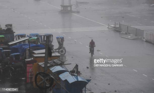 An Indian resident rides a bike along a road after Cyclone Fani landfall in Puri in the eastern Indian state of Odisha on May 3 2019 Two people died...
