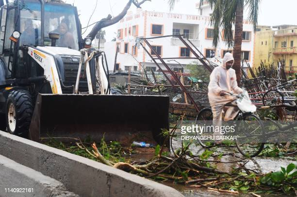 An Indian resident rides a bike past a bulldozer clearing debris from a road after Cyclone Fani landfall in Puri in the eastern Indian state of...